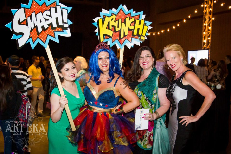4 women posing in costumes and holding comic book signs