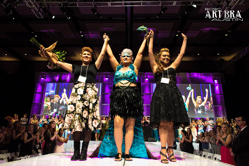 3 ladies with raised hands on fashion runway